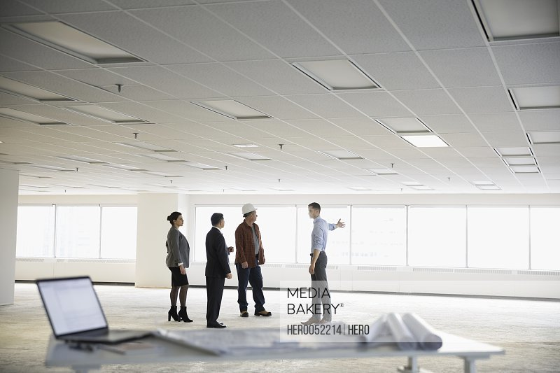 Contractor and architects working in unfinished empty open plan office