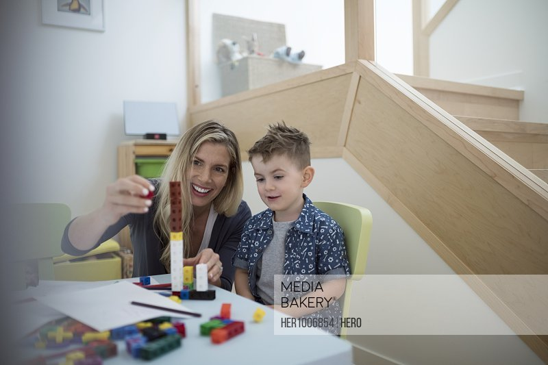 Mother and son playing, stacking plastic blocks at table
