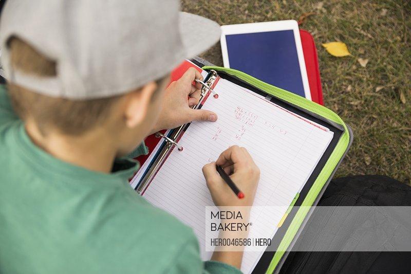Tween boy doing homework in grass
