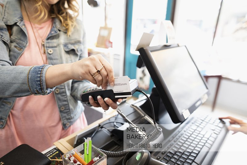 Female shopper paying with credit card, using credit card reader in shop
