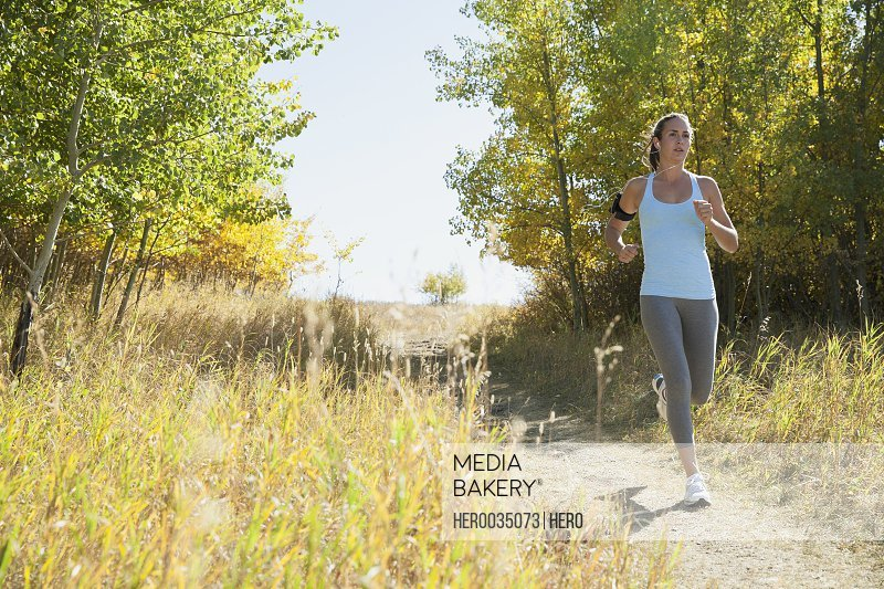Woman running outdoors on pathway.