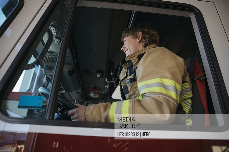 Male firefighter driving fire engine