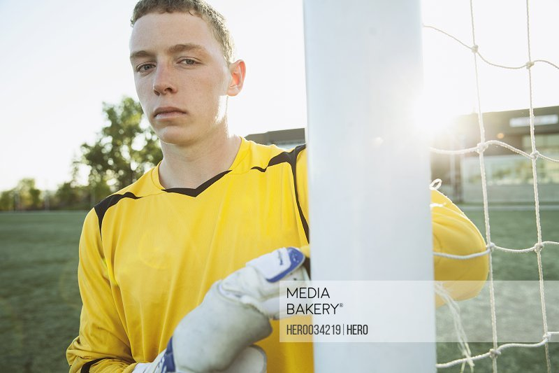 Soccer goalie with serious look by net.
