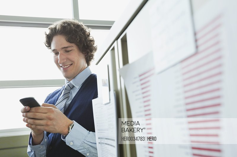 Businessman text messaging while standing by office cubicle