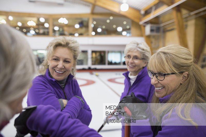 Smiling senior women talking at curling club