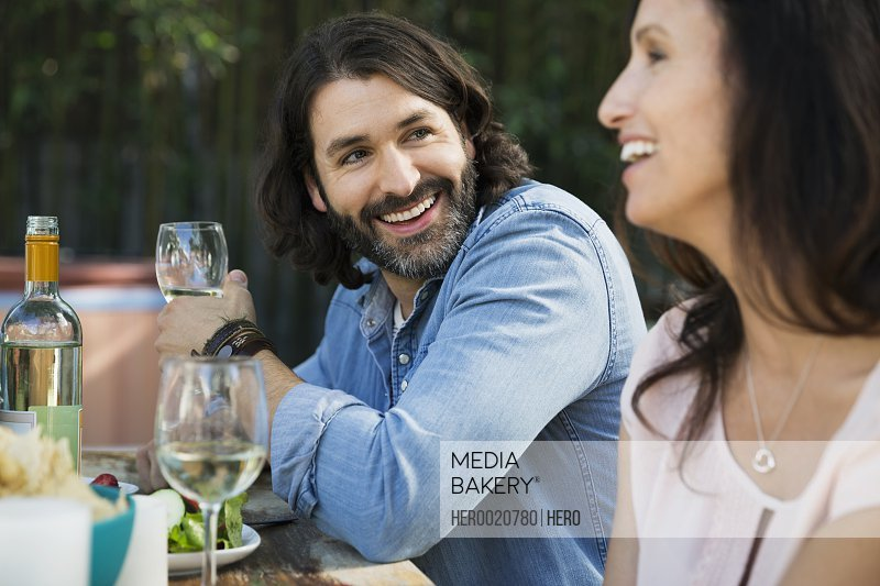 Smiling couple drinking wine at patio table