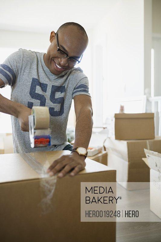 Smiling man taping moving box