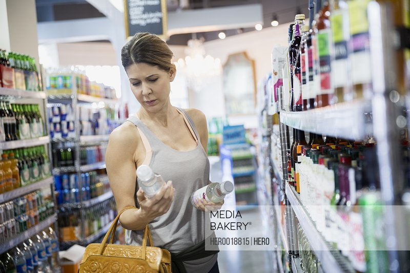 Woman reading labels on bottles in grocery store