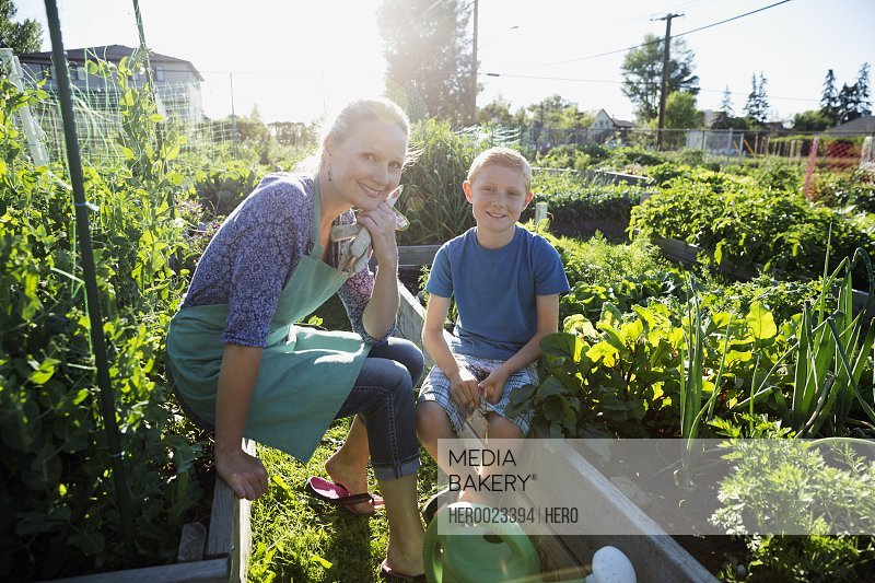 Portrait smiling mother and son sunny vegetable garden