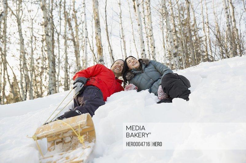 Cheerful couple tobogganing outdoors