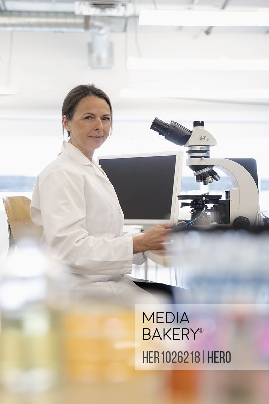 Portrait confident female scientist at microscope in laboratory