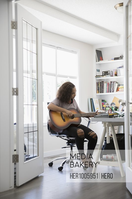 Teenage girl playing guitar in home office