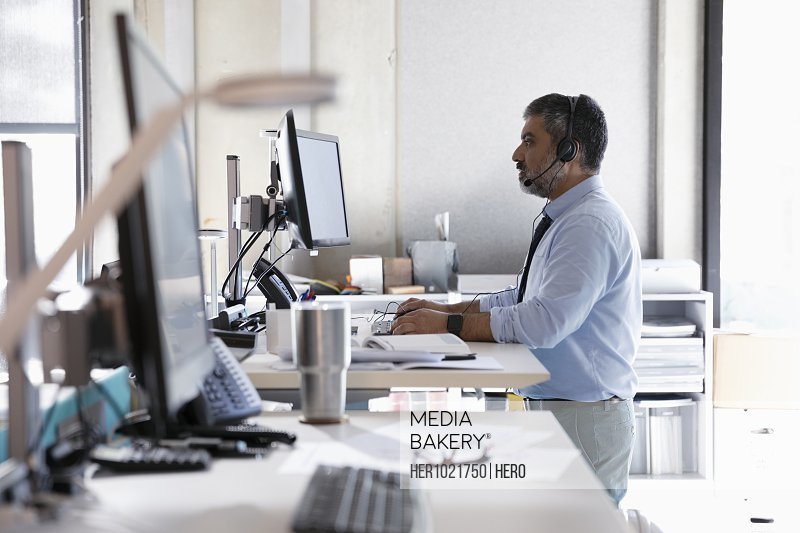 Businessman with headset using computers at sit-stand desk in office