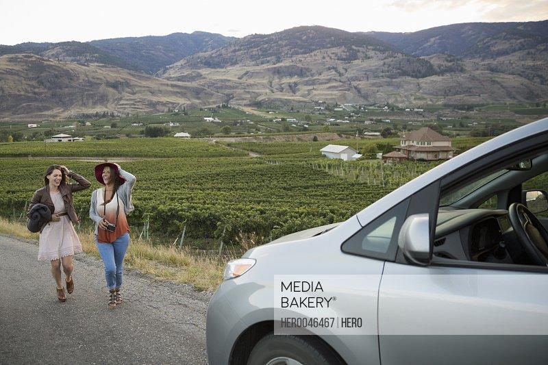 Women friends walking toward car in vineyard