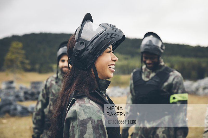 Happy young woman paintballing