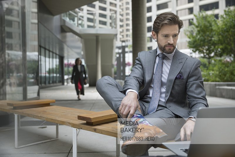 Businessman working at laptop on urban bench