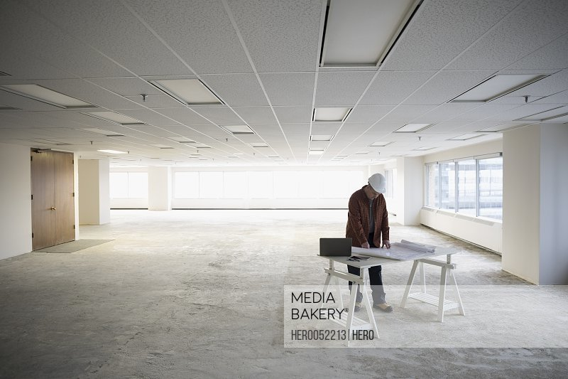 Contractor reviewing blueprints in unfinished empty open plan office