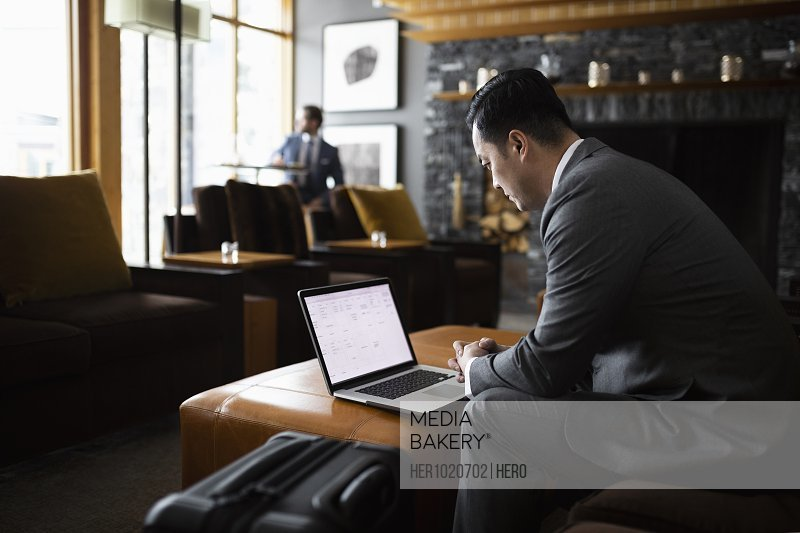 Businessman working at laptop in hotel lobby