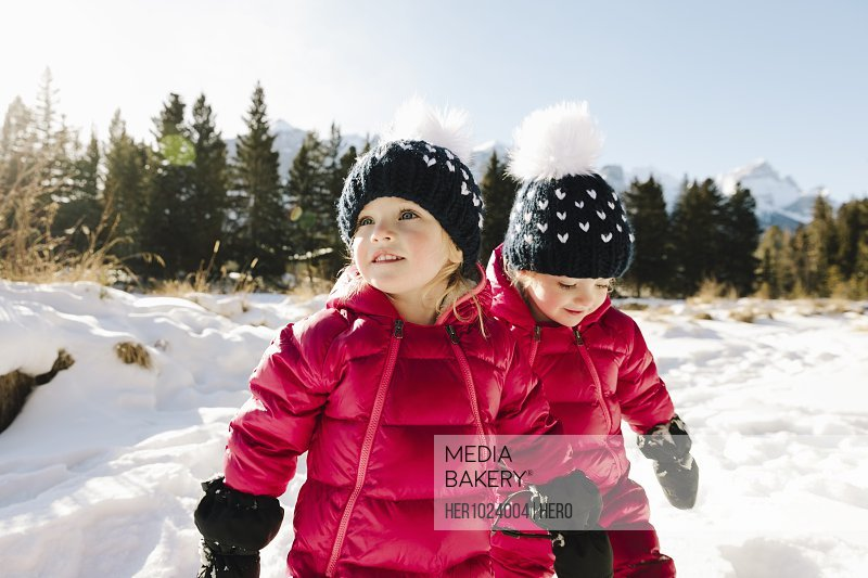 Cute toddler girl twins playing in snow