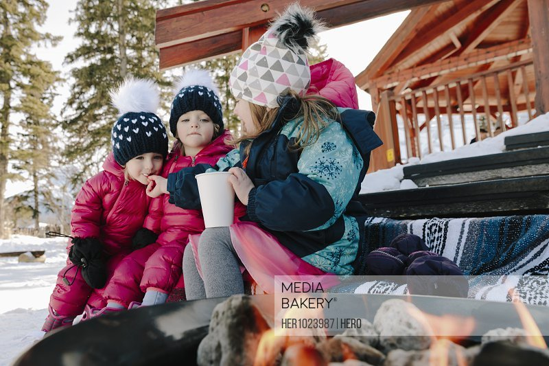 Cute girls eating by fireplace on snowy steps