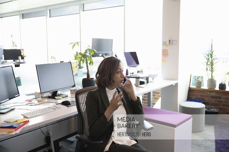 Mid adult businesswoman on cell phone in office