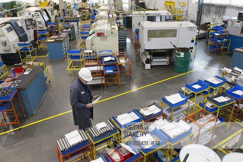 Supervisor examining equipment in machine shop