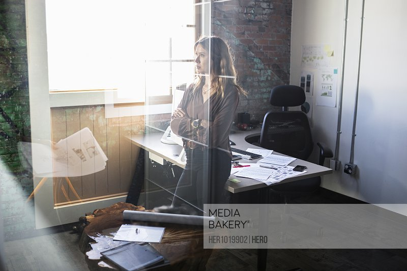 Attentive creative businesswoman listening to colleague in office