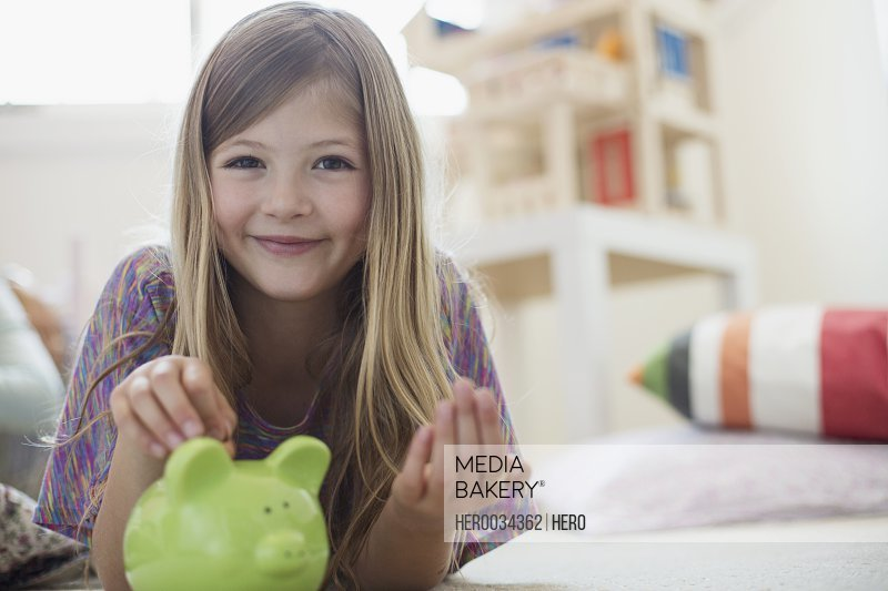 Portrait of young girl inserting coin into piggy bank at home