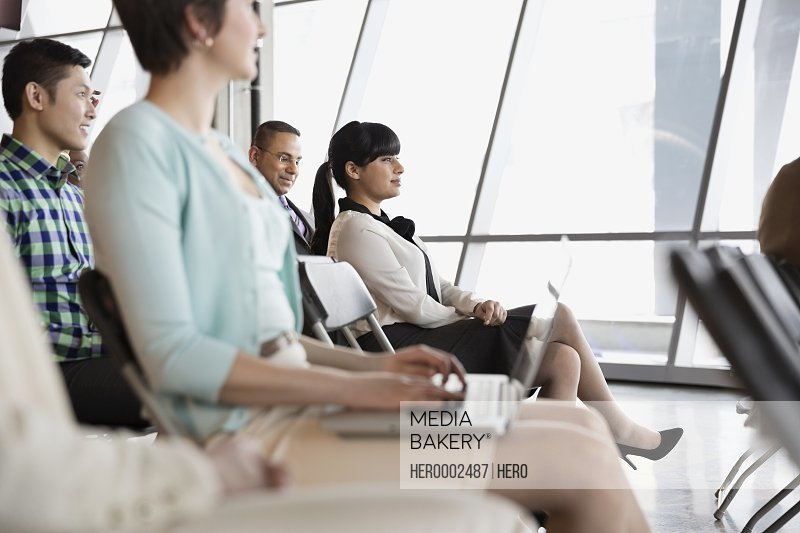 Businesspeople listening to presentation in office building