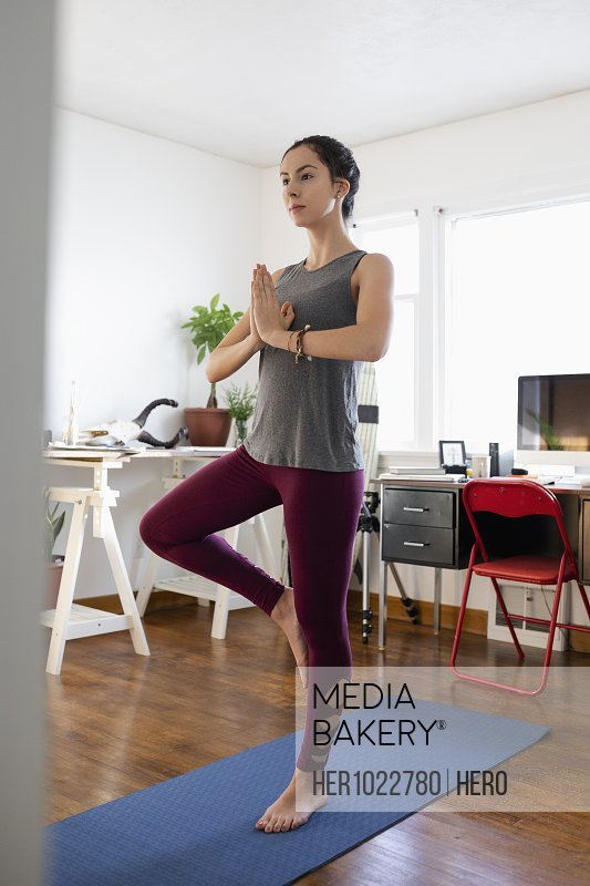 Serene young Latinx woman practicing yoga tree pose in apartment