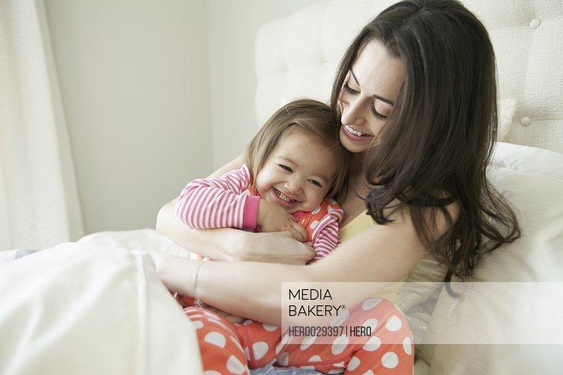mom cuddling child in bedroom