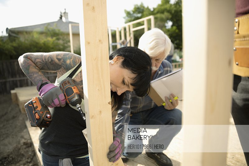 Woman with tattoos using power drill at construction site