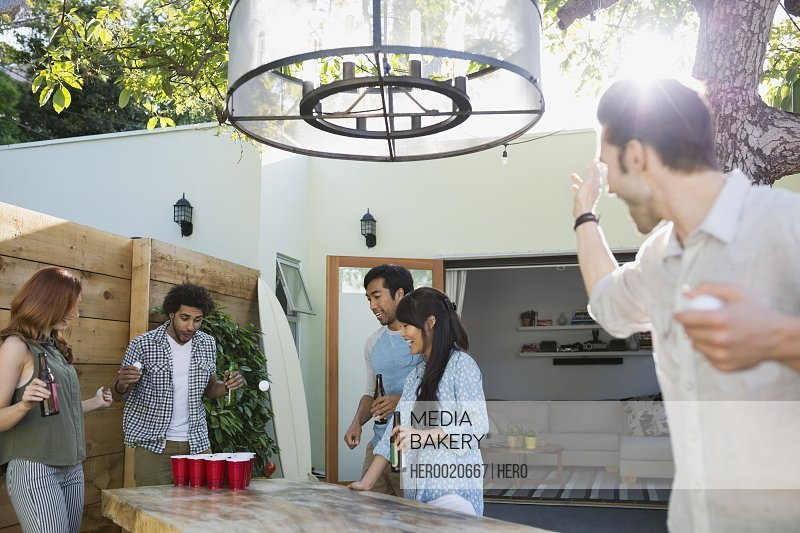 Friends playing beer pong on sunny patio