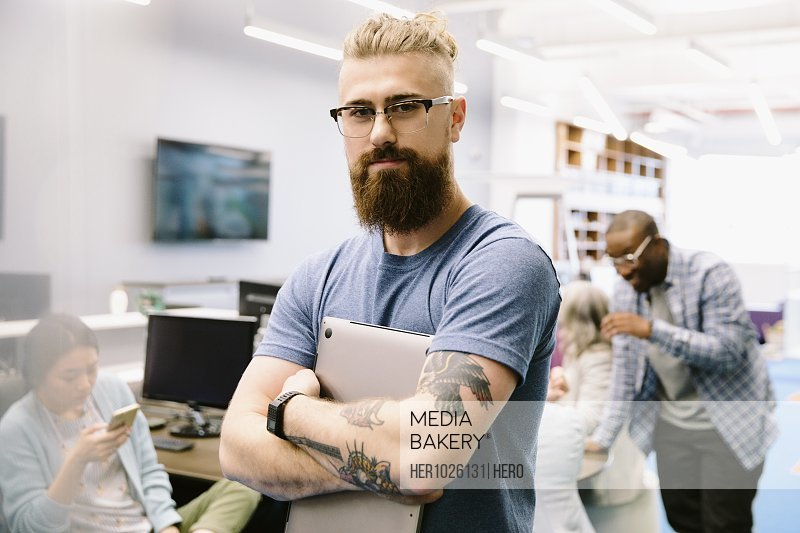 Portrait confident creative businessman with tattoos holding laptop in office