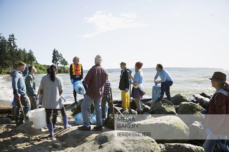 Beach cleanup volunteers on sunny beach rocks