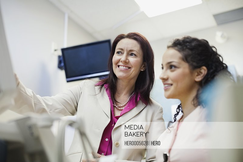 Happy female medical professional talking  with coworker in clinic