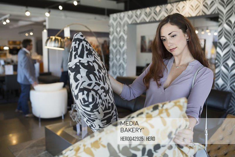 Woman browsing decorative pillows at home furnishing store