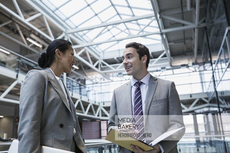 Businessman and businesswoman talking in atrium