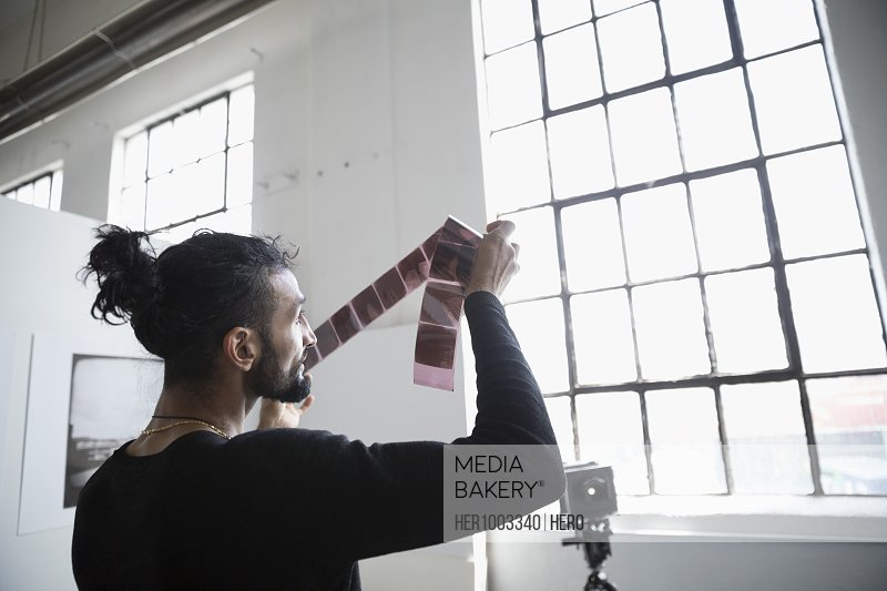 Male photographer examining photograph negatives in art studio
