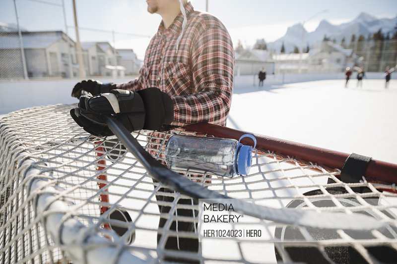 Man resting at goal, playing outdoor ice hockey
