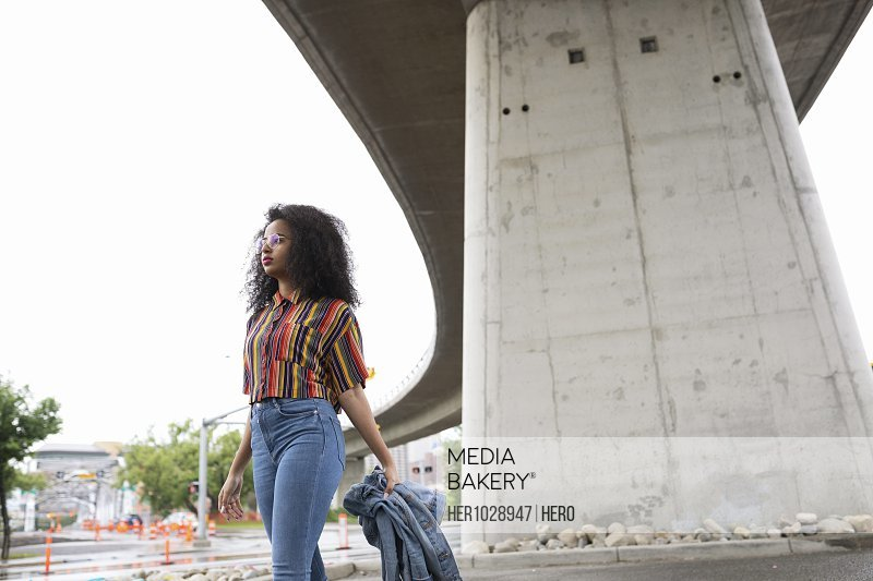 Young woman walking under city overpass