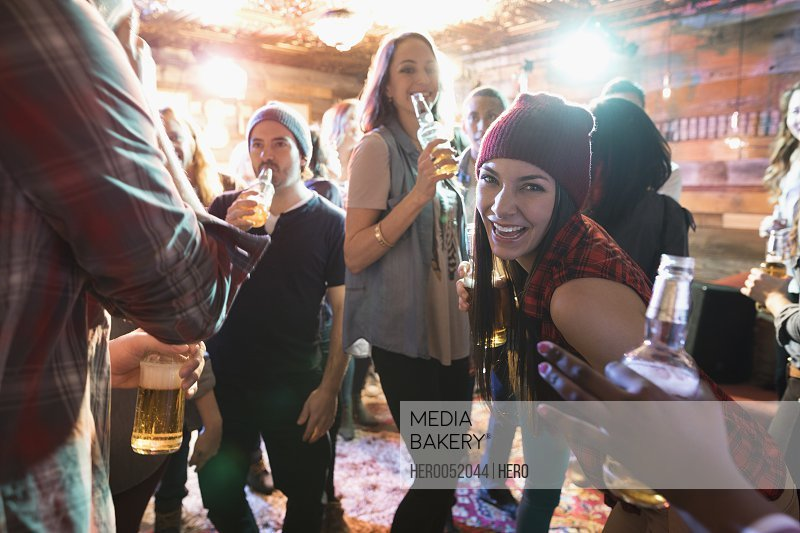 Portrait confident young woman drinking beer at party