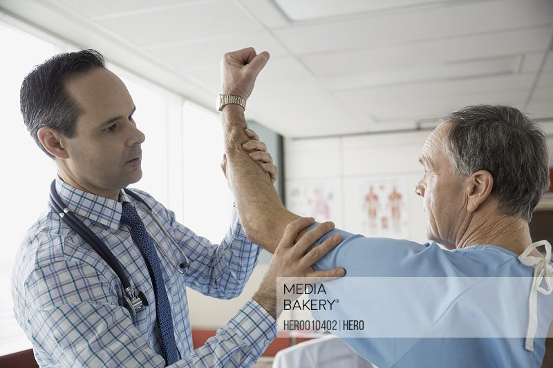 Doctor checking senior patients shoulder in office