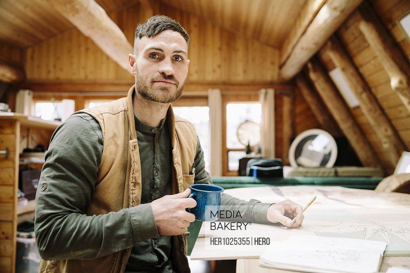 Portrait confident male artist drawing and drinking coffee at cabin table