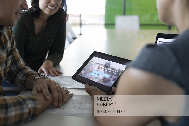 Financial advisor using tablet with couple