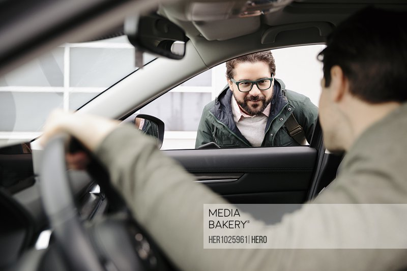 Male crowdsourced taxi driver talking with passenger at car window