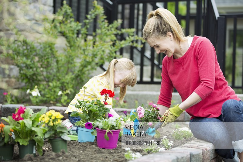 mom and 5 year old daughter planting flower bed