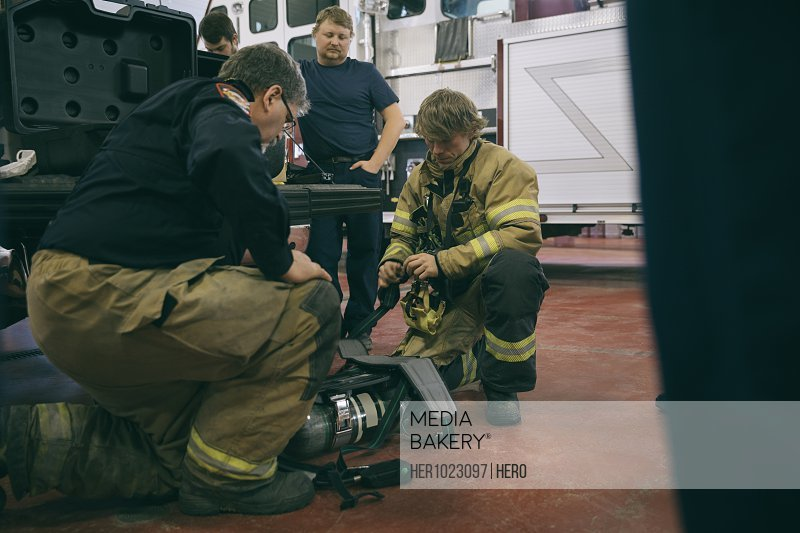 Firefighters checking equipment in fire station
