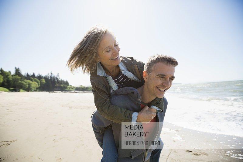 Playful couple piggybacking on sunny beach