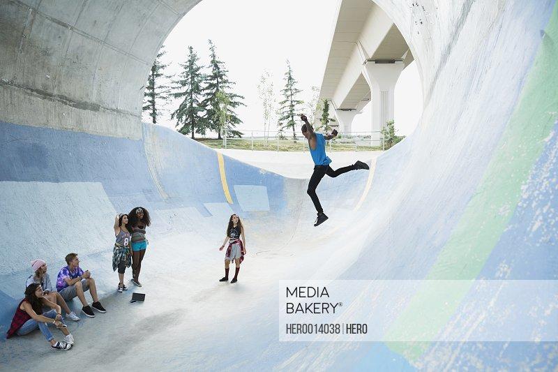 Teenage boy jumping down skateboard ramp